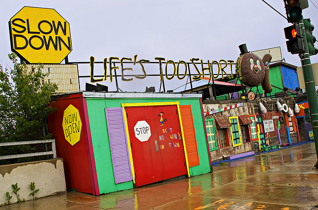 "Multicolored beach shop with sign: ""Slow Down. Life's Too Short"""